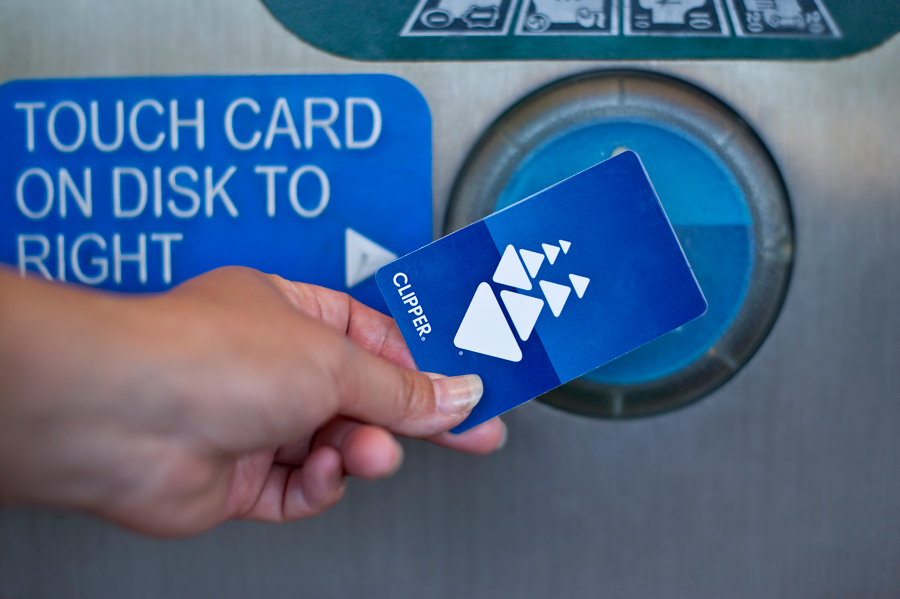 Close-up of a woman's hand holding a Clipper card over the card reader target of a transit ticket machine
