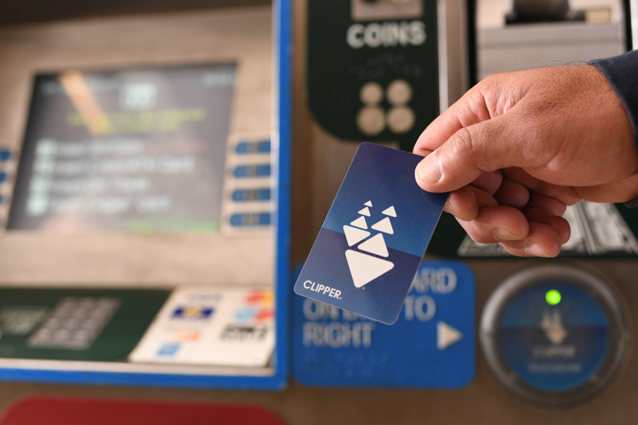 Close-up of a man's hand holding a Clipper card in front of a transit ticket machine