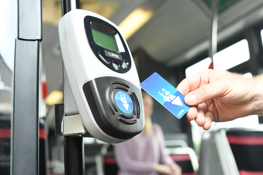 Close-up of a man's hand holding a Clipper card over a card reader mounted inside a bus
