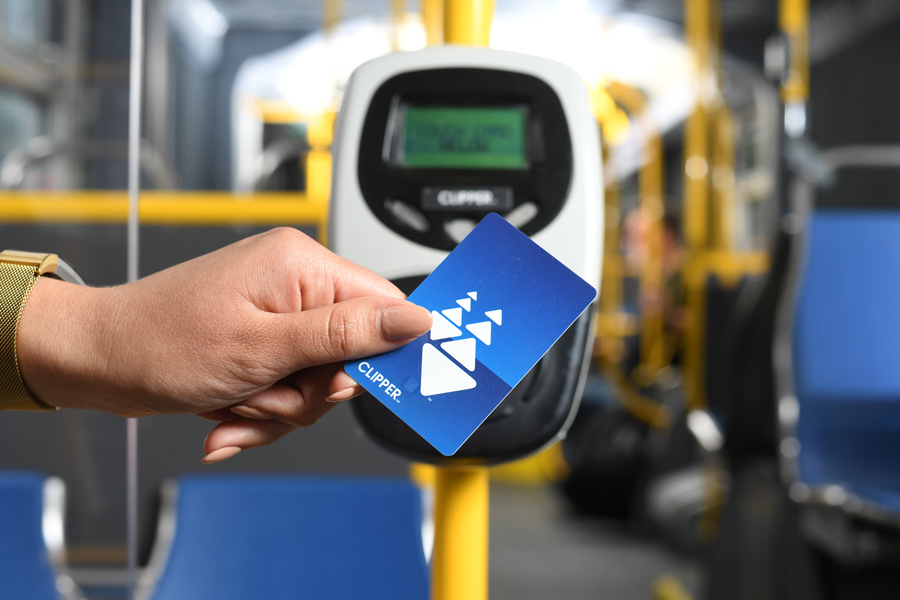 Close-up of a woman's hand holding Clipper card over a card reader mounted inside a bus