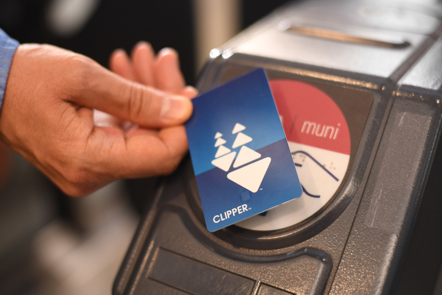 Close-up of a man's hand holding a Clipper card over the card reader target at a Muni fare gate