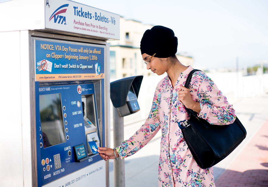 Woman holding a Clipper card at a VTA ticket machine