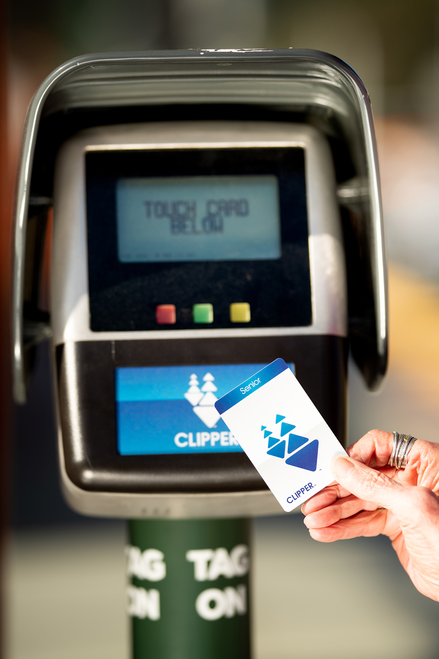 Close-up of a woman's hand holding a Senior Clipper card over a card reader on a transit platform